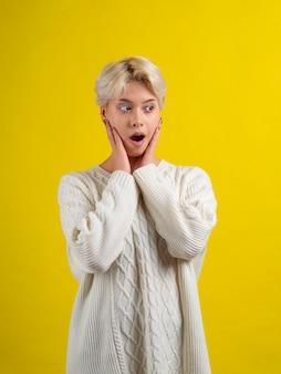 Schockiertes jugendlich mädchen mit kurzem weißen haarschnitt, der weißen strickpullover trägt