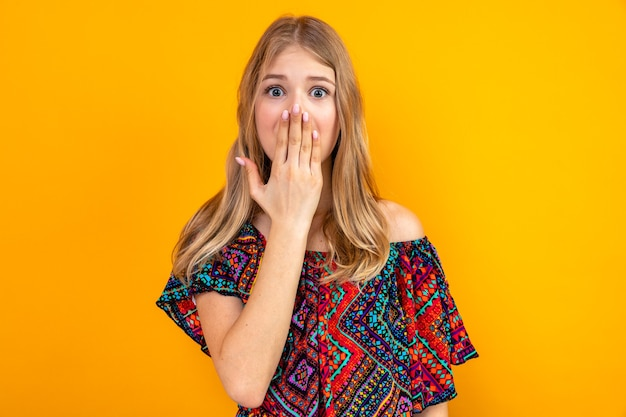 Schockiertes junges blondes slawisches mädchen, das sich die hand auf den mund legt und nach vorne schaut