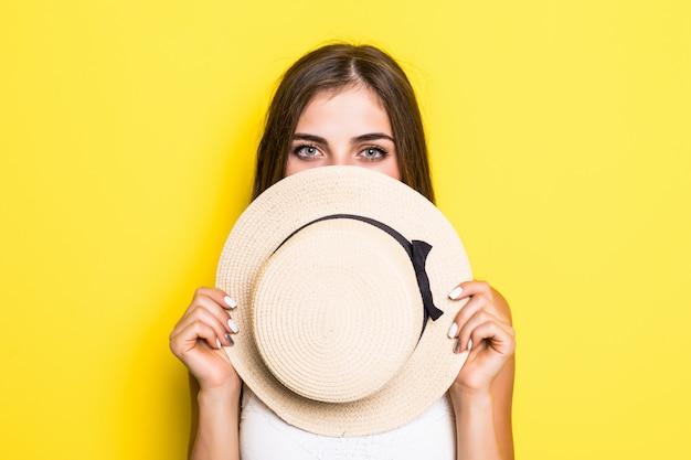 Schockiertes junges brünettes frauenmädchen im weißen kleiderhut, das lokal auf gelber wand aufwirft. menschen aufrichtige emotionen lebensstilkonzept.