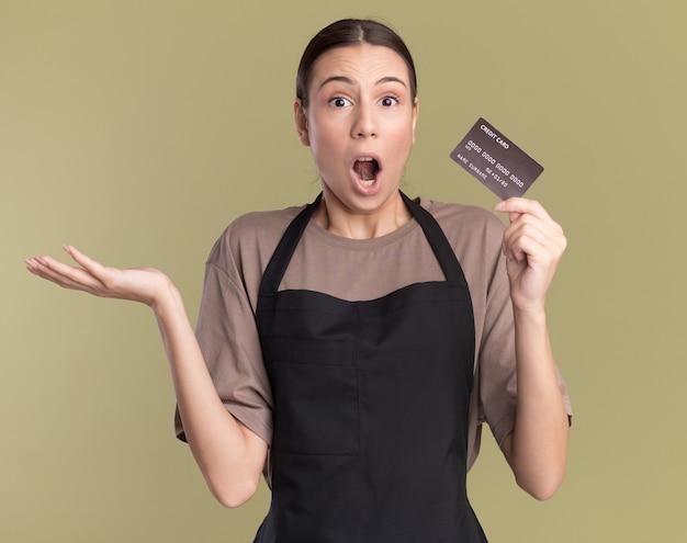 Schockiertes junges brünettes friseurmädchen in uniform hält die hand offen und hält die kreditkarte