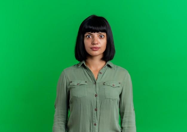 Schockiertes junges brünettes kaukasisches mädchen betrachtet kamera lokalisiert auf grünem hintergrund mit kopienraum