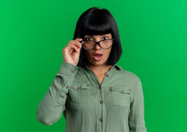Schockiertes junges brünettes kaukasisches mädchen hält optische brille, die kamera lokalisiert auf grünem hintergrund mit kopienraum betrachtet