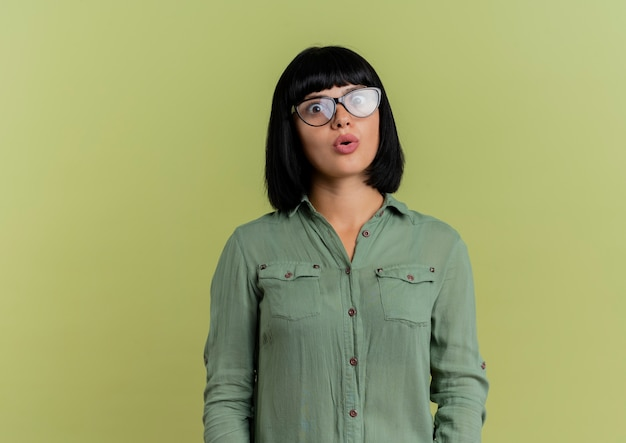 Schockiertes junges brünettes kaukasisches mädchen in optischen gläsern betrachtet kamera lokalisiert auf olivgrünem hintergrund mit kopienraum