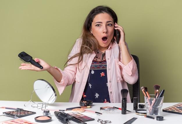 Schockiertes junges brünettes mädchen, das am tisch mit make-up-tools sitzt und am telefon spricht und das telefon hält?