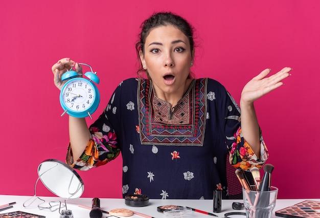 Schockiertes junges brünettes mädchen, das am tisch mit make-up-tools sitzt und wecker isoliert auf rosa wand mit kopienraum hält?