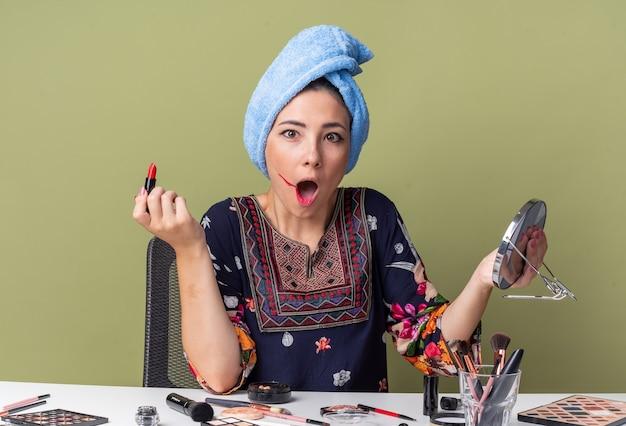 Schockiertes junges brünettes mädchen mit eingewickelten haaren im handtuch, das am tisch mit make-up-tools sitzt, die spiegel und lippenstift halten, isoliert auf olivgrüner wand mit kopierraum
