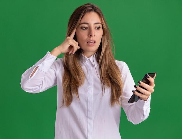 Schockiertes junges hübsches kaukasisches mädchen legt finger auf tempel, der telefon auf grün hält und betrachtet