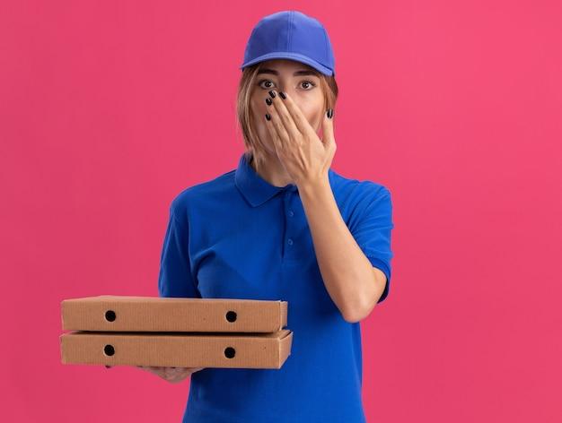 Schockiertes junges hübsches liefermädchen in uniform legt hand auf mund und hält pizzaschachteln auf rosa