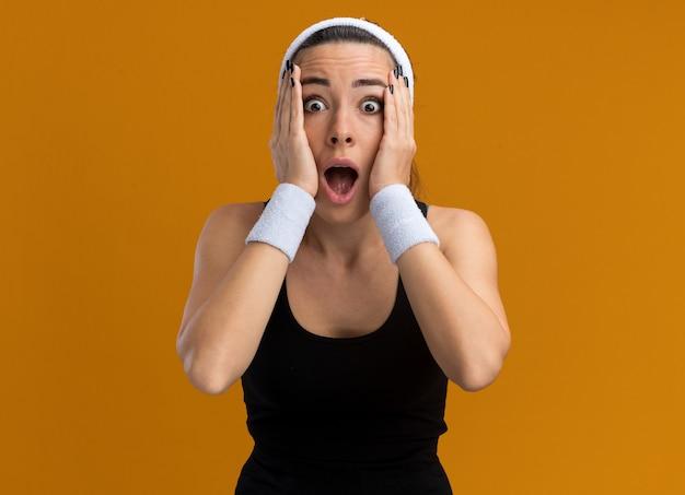 Schockiertes junges hübsches sportliches mädchen mit stirnband und armbändern, das die hände auf dem gesicht hält