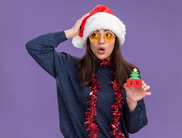 Schockiertes junges kaukasisches mädchen in der sonnenbrille mit weihnachtsmütze und girlande um den hals hält weihnachtsbaumverzierung und legt hand auf kopf, der seite lokalisiert auf lila hintergrund mit kopienraum betrachtet
