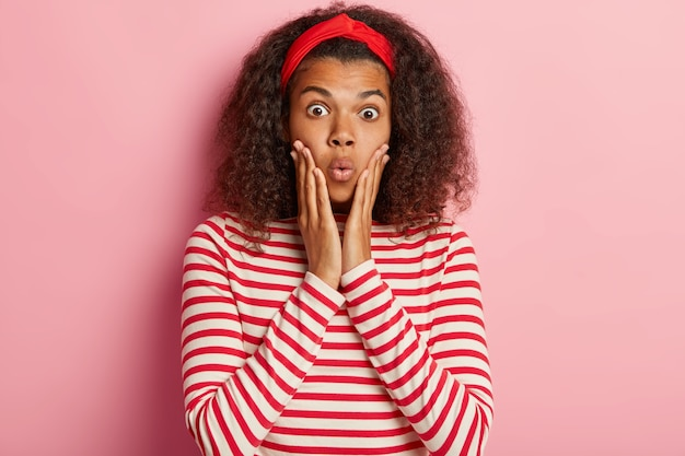 Schockiertes junges mädchen mit lockigem haar, das im gestreiften roten pullover aufwirft