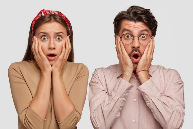 Schockiertes junges paar, das gegen die weiße wand aufwirft