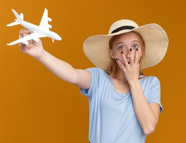 Schockiertes junges rothaariges ingwermädchen mit sommersprossen, das einen strandhut trägt, legt die hand auf den mund und hält das modellflugzeug