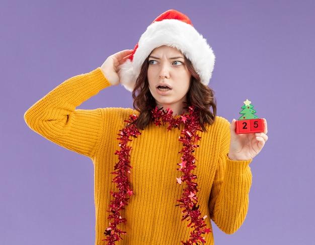 Schockiertes junges slawisches mädchen mit weihnachtsmütze und mit girlande um hals, der weihnachtsbaumverzierung hält und seite lokalisiert auf lila hintergrund mit kopienraum betrachtet
