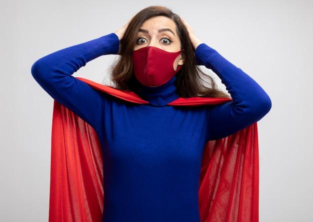 Schockiertes kaukasisches superheldenmädchen mit rotem umhang mit roter schutzmaske legt die hände auf den kopf und schaut in die kamera