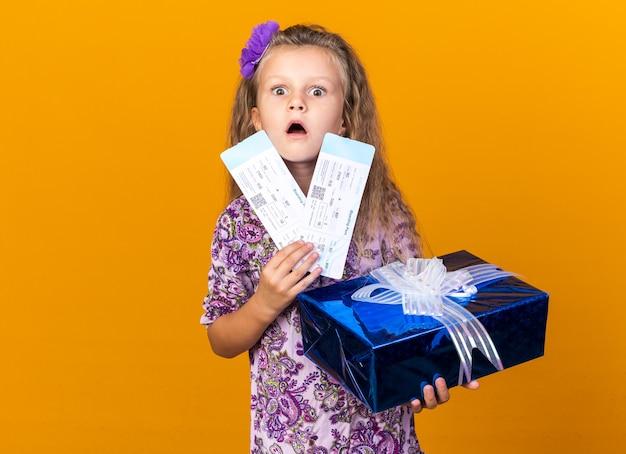 Schockiertes kleines blondes mädchen, das geschenkbox und flugtickets lokalisiert auf orange wand mit kopienraum hält