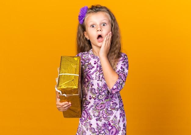 Schockiertes kleines blondes mädchen, das hand auf gesicht setzt und geschenkbox lokalisiert auf orange wand mit kopienraum hält