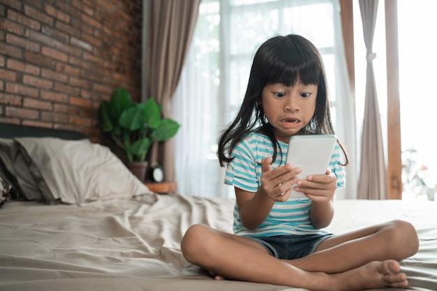 Schockiertes kleinkind beim betrachten ihres handys