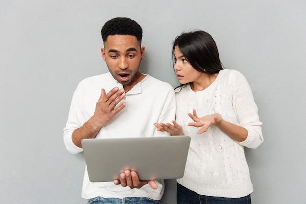 Schockiertes liebespaar, das durch laptop-computer plaudert