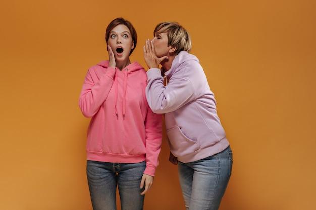 Schockiertes mädchen in jeans und breitem rosa kapuzenpulli, das geheimnis von ihrer großmutter in stilvollen kleidern auf orange hintergrund hört.