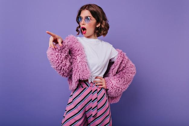 Schockiertes mädchen mit glänzendem gewelltem haar, das auf lila wand in pelzjacke steht. innenaufnahme des weiblichen modells im rosa outfit, das emotional aufwirft