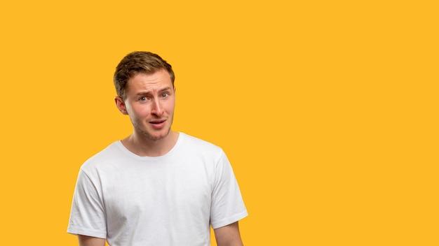 Schockiertes mannporträt. anzeigenhintergrund. zweifelhafter kerl isoliert auf orangefarbenem kopienraum.