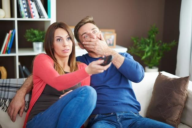 Schockiertes paar beim anschauen eines gruselfilms