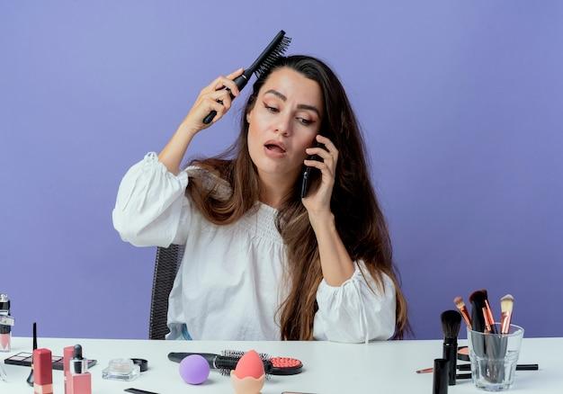 Schockiertes schönes mädchen sitzt am tisch mit make-up-werkzeugen, die haare kämmen, die am telefon lokalisiert auf lila wand sprechen