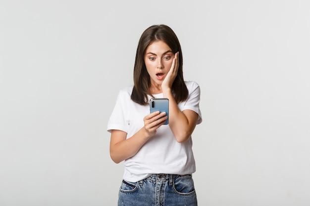 Schockiertes und beeindrucktes brünettes mädchen, das erstaunt auf den smartphonebildschirm schaut.