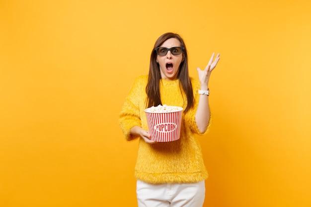 Schockiertes verängstigtes junges mädchen in 3d-imax-brille, das schreit, hände ausbreitet, filmfilm sieht, der popcorn einzeln auf hellgelbem hintergrund hält. menschen aufrichtige emotionen im kino, lifestyle-konzept.