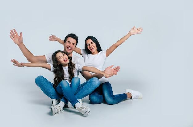 Schön aufgeregt und das lustige familienteam posiert in einem weißen t-shirt, während sie im studio auf weißem hintergrund isoliert sind.