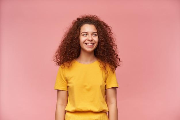 Schön aussehende frau mit lockigem ingwerhaar, das gelbes t-shirt trägt