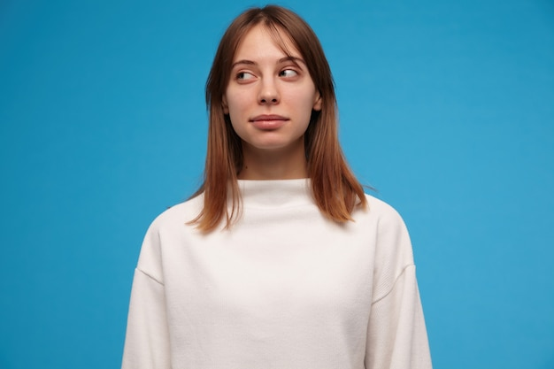 Schön aussehende frau, schönes mädchen mit brünetten haaren. trage einen weißen pullover. personenkonzept. lässig aussehend. verdächtig nach links im kopierraum beobachten, isoliert über der blauen wand