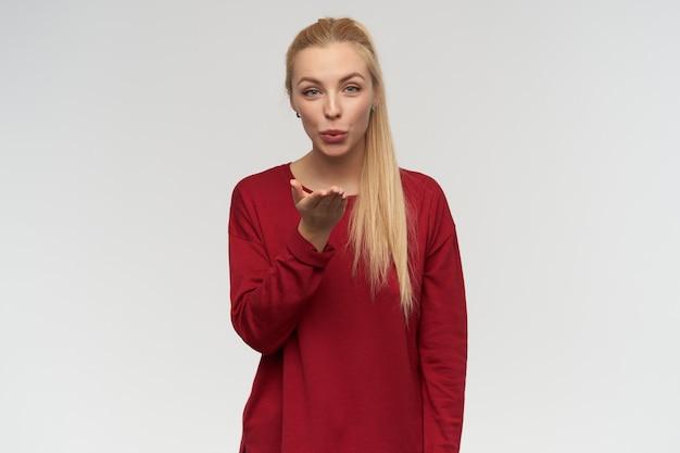 Schön aussehende frau, schönes mädchen mit langen blonden haaren. trage einen roten pullover. menschen- und emotionskonzept. beobachten sie in die kamera, isoliert über weißem hintergrund, senden sie einen kuss