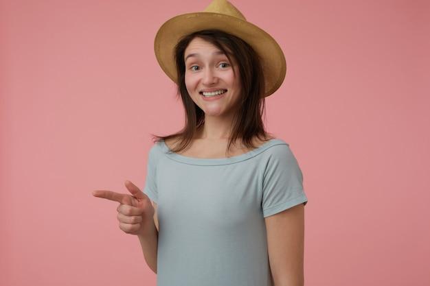 Schön aussehende frau, schönes mädchen mit langen brünetten haaren. trägt ein bläuliches t-shirt und einen hut. nach links auf den kopierbereich über der pastellrosa wand zeigen