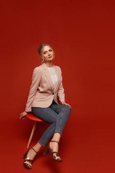 Schön aussehende junge frau, die einen beigen blazer und jeans trägt, die auf dem stuhl sitzen, lokalisiert über einem roten hintergrund mit kopienraum