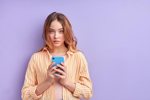 Schön aussehendes fokussiertes mädchen, das isolierte cell-web-app verwendet, attraktive frau in freizeitkleidung, die nach dem lesen der nachricht nach vorne schaut und posiert. moderne technologien