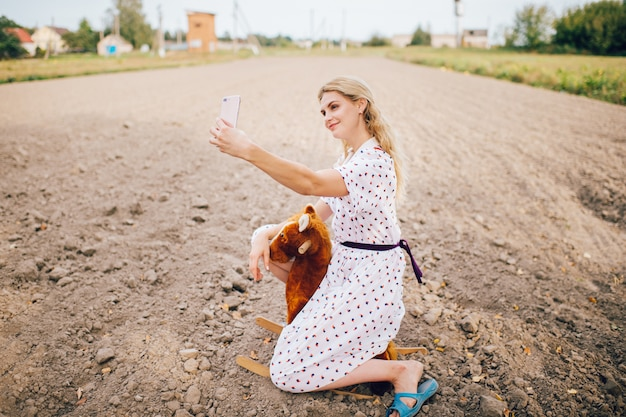 Schön aussehendes schönes blondes mädchen, das selfie foto auf smartphone macht, während auf spielzeugpferd im feld sitzt.