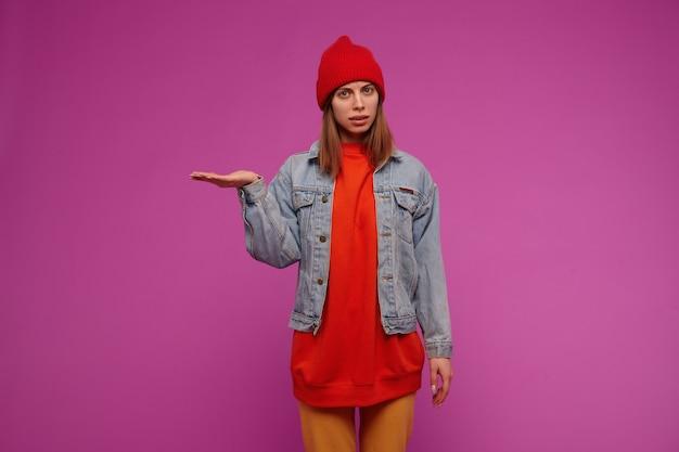 Schön aussehendes schönes mädchen mit brünetten haaren. trägt jeansjacke, gelbe hose, roten pullover und hut. stellen sie sich vor, sie halten etwas auf einer handfläche über einer lila wand