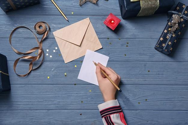 Schön dekorierte geschenkboxen und frau, die grußkarte auf holzuntergrund unterschreibt