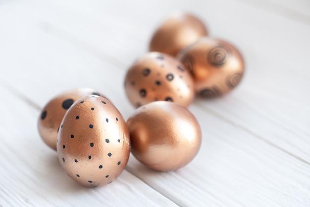 Schön dekorierte ostereier der goldenen farbe mit schwarzen punkten
