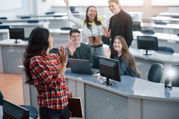 Schön dich zu sehen. gruppe junger leute in freizeitkleidung, die im modernen büro arbeiten