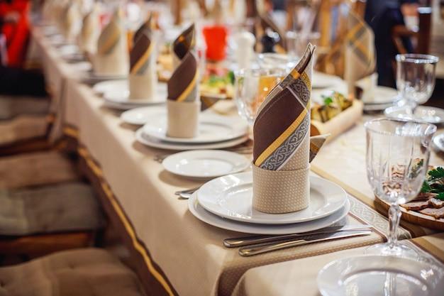 Schön gefaltete servietten auf einem gedienten tisch. brown-servietten auf einer weißen platte. feier im restaurant. cafe party beim bankett.