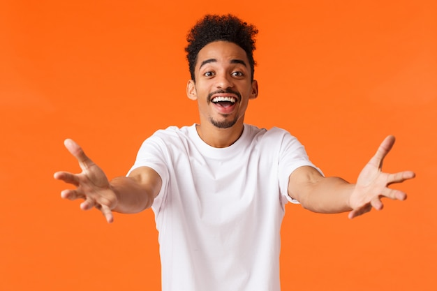 Schön und fürsorglich, afroamerikaner freund gefühl liebe wollen jemanden umarmen, streckte die arme in richtung für umarmung, halten oder schnappen sie sich etwas kostbares, glücklich lächelnd, orange wand