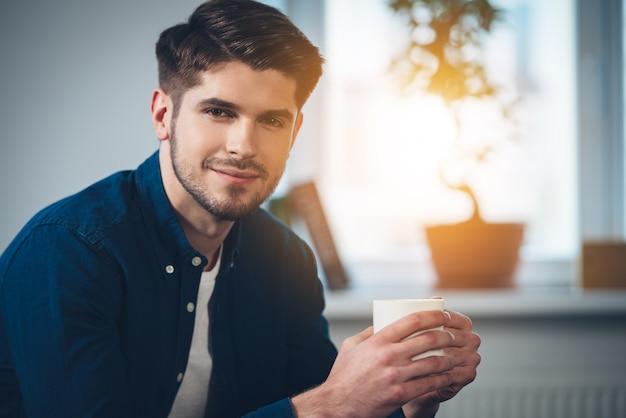 Schön und ruhig. nahaufnahme eines gutaussehenden jungen mannes, der eine kaffeetasse mit einem lächeln hält