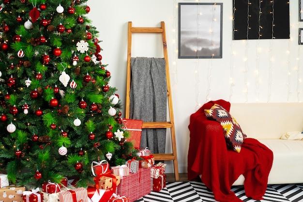 Schön verzierter weihnachtsraum mit tannenbaum und weißem sofa