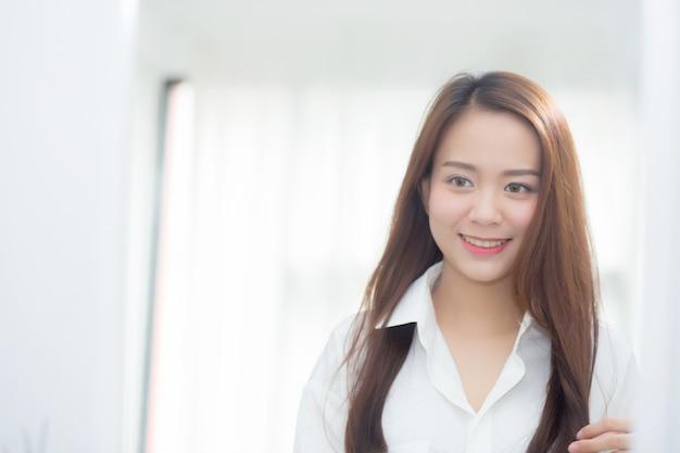 Schön von der asiatischen frau des porträts, die mit gesicht und lächeln überprüft
