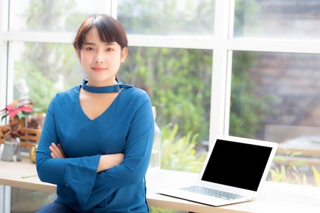 Schön von der asiatischen jungen frau des porträts, die kamera und laptop schauend sitzt