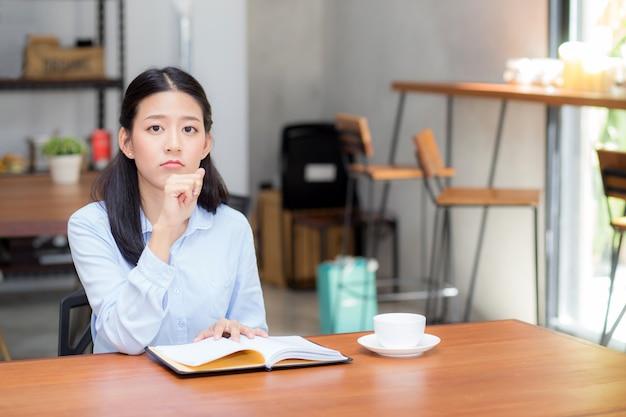 Schön von der denkenden idee der asiatischen frau des porträtgeschäfts und schreiben auf notizbuch