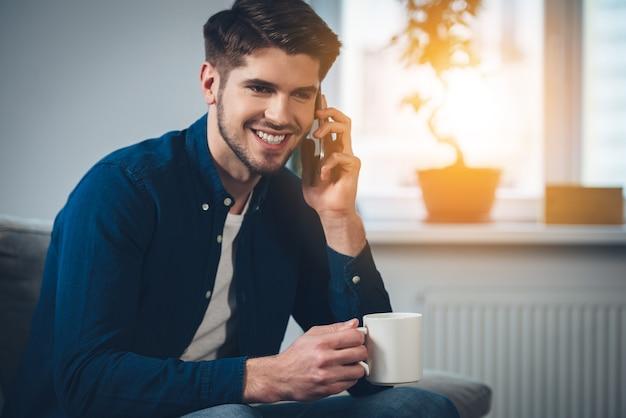 Schön von dir zu hören! hübscher junger mann, der mit einem lächeln auf dem handy spricht und eine kaffeetasse hält holding